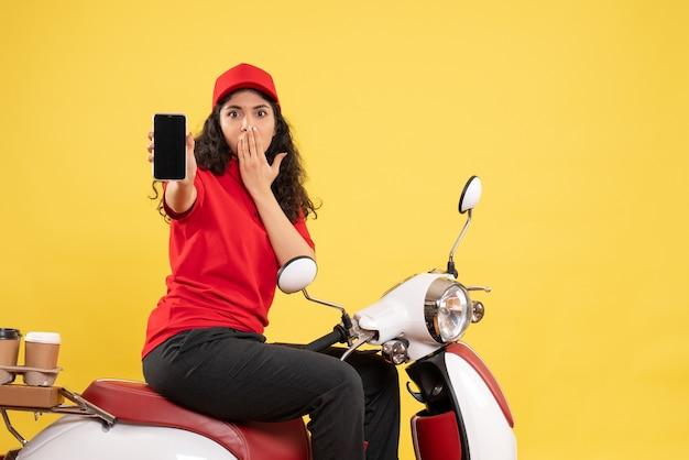 Vooraanzicht vrouwelijke koerier op de fiets voor koffiebezorging met telefoon op gele achtergrond servicebezorging uniforme baan werknemer werk vrouw