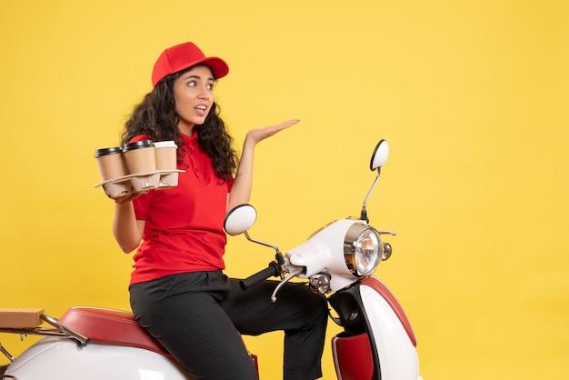 Vooraanzicht vrouwelijke koerier op de fiets voor koffiebezorging op de gele achtergrond baanservice uniforme werknemer vrouw bezorgwerk