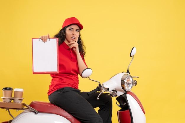 Vooraanzicht vrouwelijke koerier op de fiets voor koffiebezorging op een gele achtergrond bezorging uniforme baan werknemer service werk vrouw eten