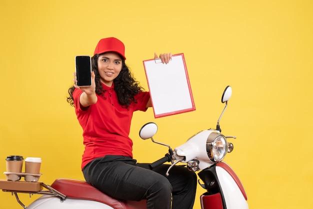 Vooraanzicht vrouwelijke koerier op de fiets voor koffiebezorging op gele achtergrond bezorging baan werknemer service werk vrouw eten