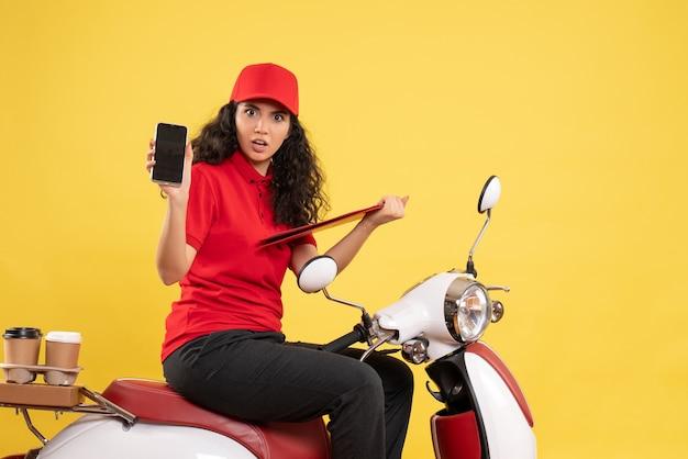 Vooraanzicht vrouwelijke koerier op de fiets voor koffiebezorging op gele achtergrond bezorging uniforme baanservice werk vrouw eten