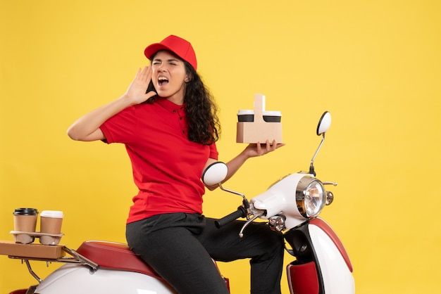 Vooraanzicht vrouwelijke koerier op de fiets voor koffiebezorging op gele achtergrond dienstbezorger werkvrouw werkvrouw
