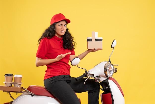 Vooraanzicht vrouwelijke koerier op de fiets voor koffiebezorging op gele achtergrond dienstverlening uniforme baan werk vrouw