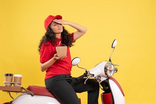Vooraanzicht vrouwelijke koerier op de fiets voor koffiebezorging op gele achtergrond servicebezorging uniforme werkvrouw vrouw