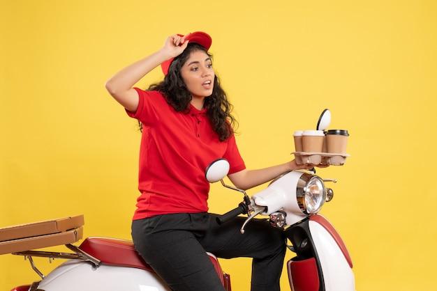Vooraanzicht vrouwelijke koerier op fiets met koffiekopjes op gele achtergrond service uniforme baan vrouw bezorgwerk