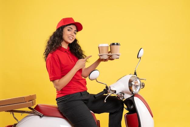 Vooraanzicht vrouwelijke koerier op fiets met koffiekopjes op gele achtergrond werknemer service uniforme baan vrouw levering werk