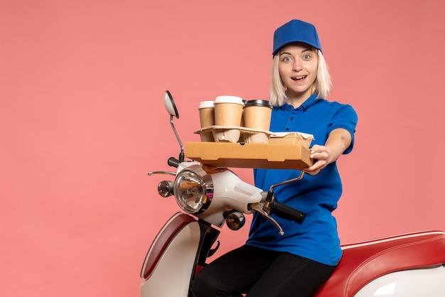 Vooraanzicht vrouwelijke koerier op fiets met koffiekopjes op roze