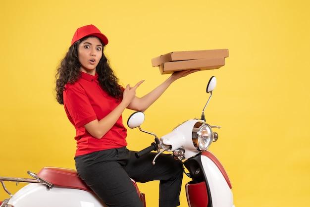 Vooraanzicht vrouwelijke koerier op fiets met pizzadozen op gele achtergrond baan service uniform werknemer vrouw werk