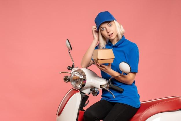 Vooraanzicht vrouwelijke koerier op fiets met weinig voedselpakket op roze