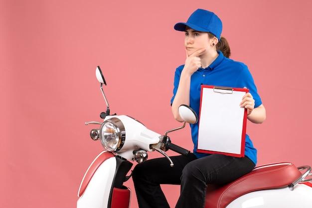 Vooraanzicht vrouwelijke koerier zittend op de fiets met bestandsnota op roze kleur uniform dienst levering baan werknemer voedsel