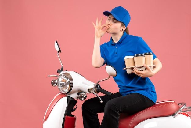 Vooraanzicht vrouwelijke koerier zittend op de fiets met koffiekopjes op de roze baan kleur uniforme bezorger foodservice