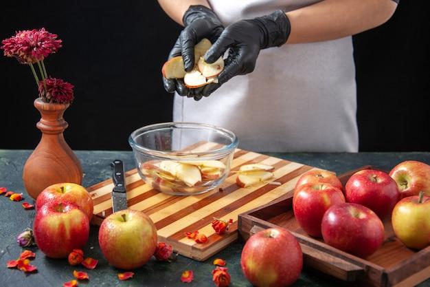 Vooraanzicht vrouwelijke kok die appels in plaat zet op donker vruchtensap dieet salade voedsel maaltijd exotisch werk taart taart