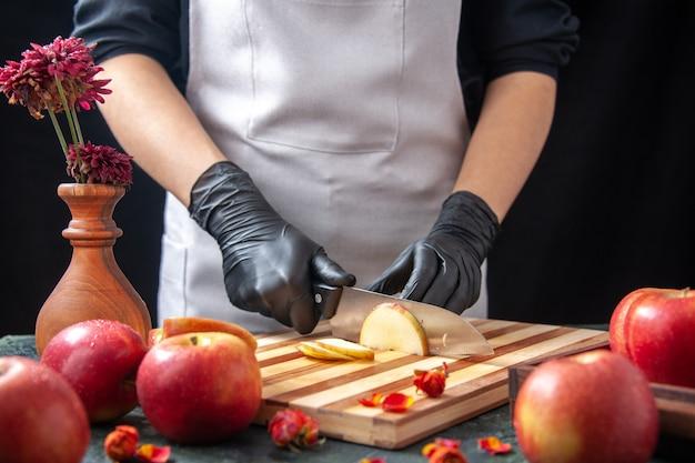 Vooraanzicht vrouwelijke kok die appels snijdt op een donkere groentedieetsalade voedselmaaltijd exotisch drankje fruit