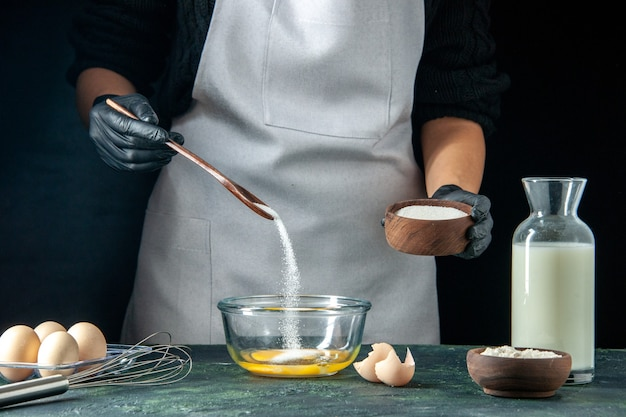 Vooraanzicht vrouwelijke kok die bloem in de eieren giet voor deeg op donkere gebak taart taart bakkerij werknemer hotcakes keuken baan