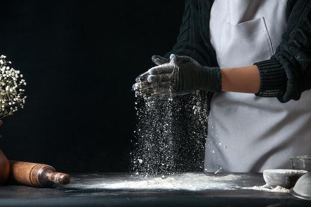 Vooraanzicht vrouwelijke kok die bloem op tafel giet voor deeg op donker deeg ei keuken baan bakkerij hotcakes gebak keuken