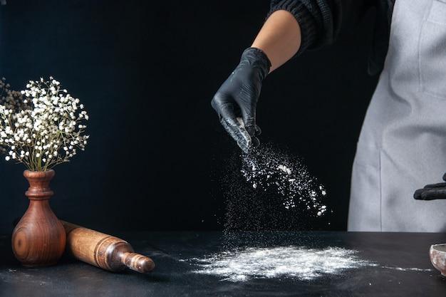 Vooraanzicht vrouwelijke kok die bloem op tafel giet voor deeg op een donker ei keuken baan gebak bakkerij keuken deeg hotcake