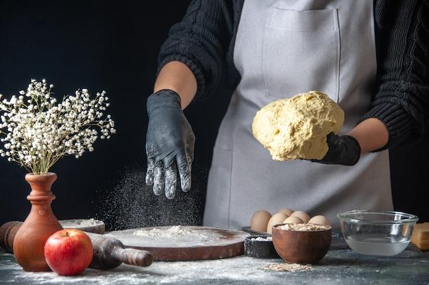 Vooraanzicht vrouwelijke kok die deeg uitrolt met bloem op de donkere baan deeg gebak keuken hotcake keuken bakkerij ei