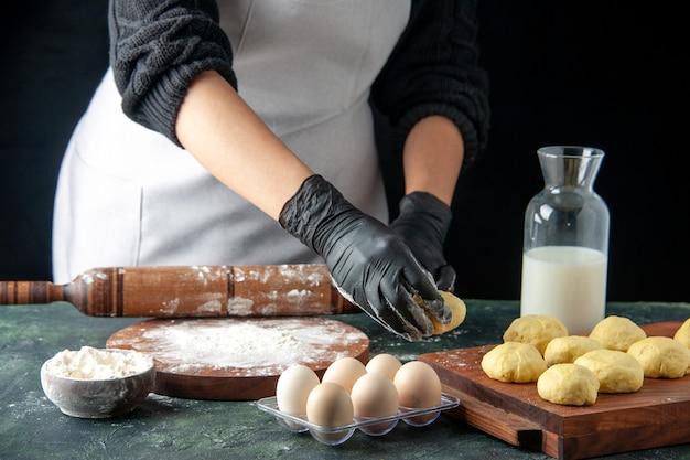 Vooraanzicht vrouwelijke kok die deeg uitrolt met bloem op de donkere baan keuken oven hotcake deeg bak cake taart werknemer ei