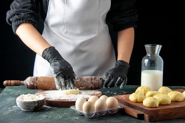 Vooraanzicht vrouwelijke kok die deeg uitrolt met bloem op de donkere cake baan oven hotcake deeg bak taart werknemer ei keuken