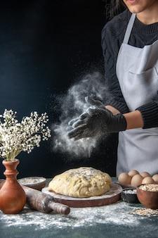 Vooraanzicht vrouwelijke kok die deeg uitrolt met bloem op donkere baan deeg bakkerij taart oven gebak hotcake