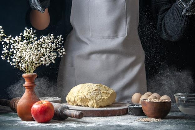 Vooraanzicht vrouwelijke kok die deeg uitrolt met bloem op donkere baan deeg gebak hotcake keuken bakkerij ei keuken