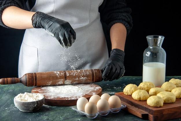 Vooraanzicht vrouwelijke kok die deeg uitrolt met bloem op donkere baan keuken hotcake rauw deeg bak cake taart werknemer eieren