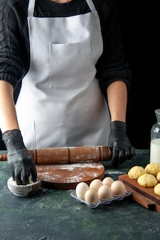 Vooraanzicht vrouwelijke kok die deeg uitrolt met bloem op donkere baan keuken hotcake rauw deeg bak cake taart werknemer