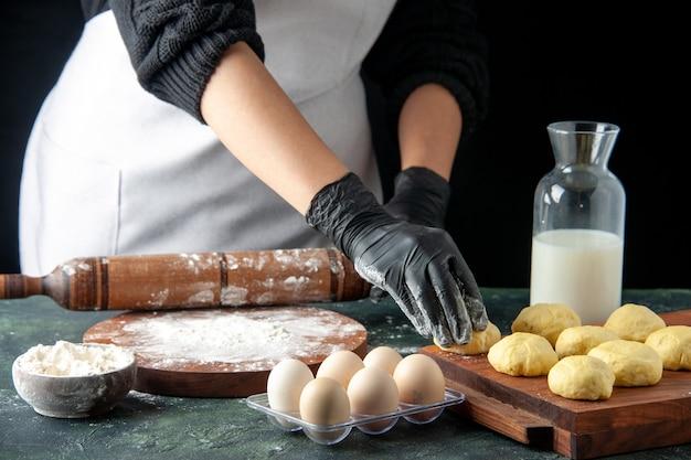 Vooraanzicht vrouwelijke kok die deeg uitrolt met bloem op donkere baan keuken hotcake rauw deeg bak cake taarten werknemer ei