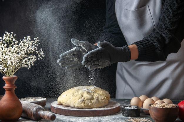 Vooraanzicht vrouwelijke kok die deeg uitrolt met bloem op donkere baan rauw deeg bakkerij taart oven gebak hotcakes