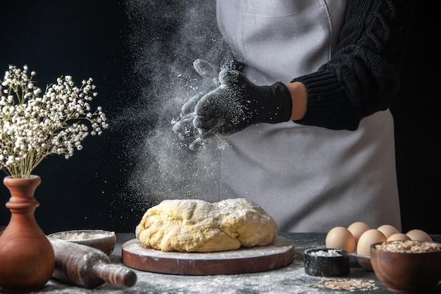 Vooraanzicht vrouwelijke kok die deeg uitrolt met bloem op donkere baan rauw deeg hotcake bakkerij taartoven