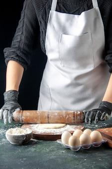 Vooraanzicht vrouwelijke kok die deeg uitrolt met bloem op donkere cake baan oven hotcake bak taart werknemer ei keuken deeg