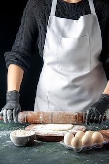 Vooraanzicht vrouwelijke kok die deeg uitrolt met bloem op donkere cake baan oven hotcake bak werknemer ei keuken deeg