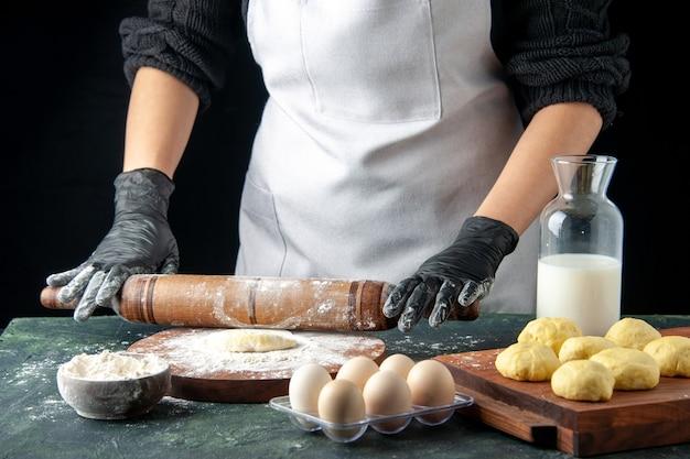 Vooraanzicht vrouwelijke kok die deeg uitrolt met bloem op donkere cake baan oven hotcake deeg bak taart werknemer eieren keuken