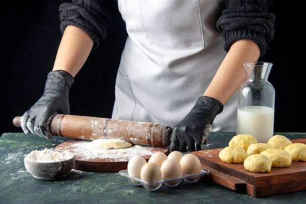 Vooraanzicht vrouwelijke kok die deeg uitrolt met bloem op donkere cake baan oven hotcake deeg taart werknemer ei keuken