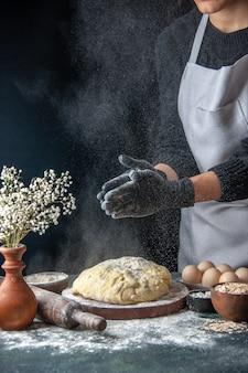Vooraanzicht vrouwelijke kok die deeg uitrolt met bloem op een donkere baan rauw deeg taart oven gebak hotcake bakkerij