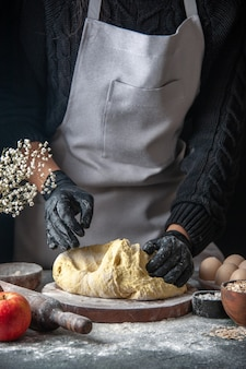 Vooraanzicht vrouwelijke kok die deeg uitrolt op donker ei keuken baan gebak bakkerij keuken deeg hotcake