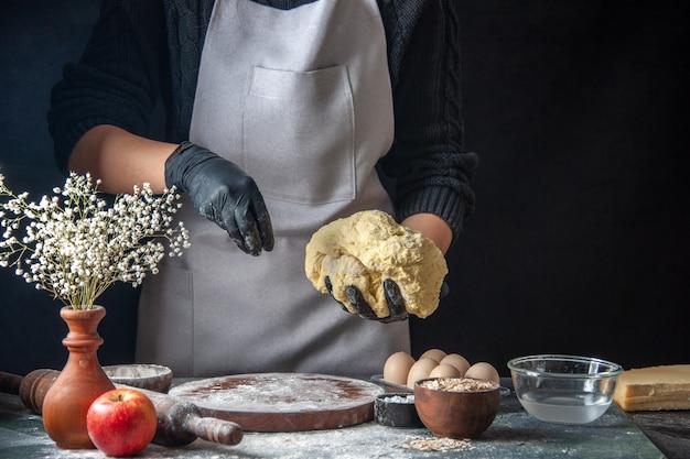 Vooraanzicht vrouwelijke kok die deeg uitrolt op donkere baan rauw deeg taart oven hotcake bakkerij ei