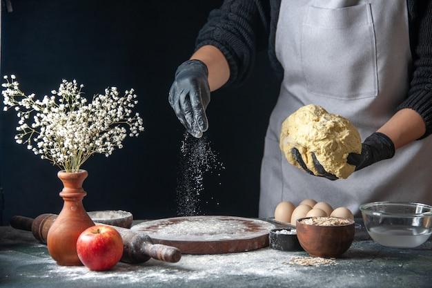 Vooraanzicht vrouwelijke kok die deeg uitrolt op donkere baan rauwe taart oven gebak hotcake bakkerij ei