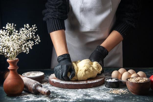 Vooraanzicht vrouwelijke kok die deeg uitrolt op donkere banketbaan rauw deeg hotcake bakkerij taarten oven