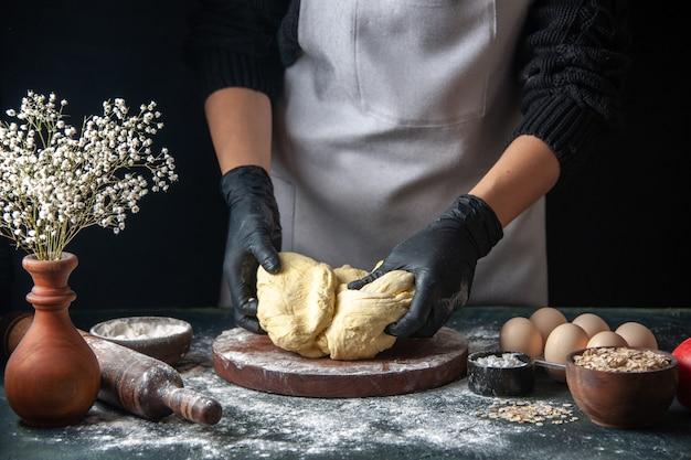 Vooraanzicht vrouwelijke kok die deeg uitrolt op donkere banketbaan rauw deeg hotcake bakkerijtaart