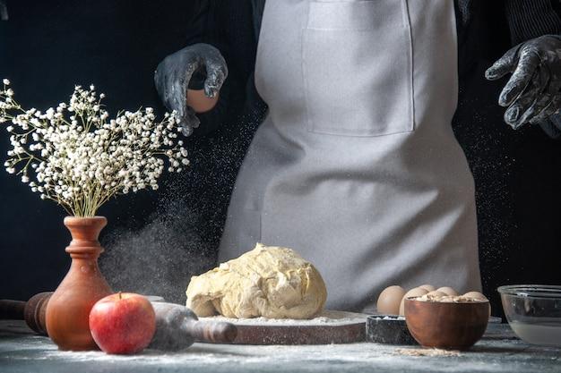 Vooraanzicht vrouwelijke kok die deeg uitrolt op donkere keuken baan gebak hotcakes bakkerij ei keuken deeg