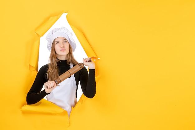 Vooraanzicht vrouwelijke kok die deegroller vasthoudt en denkt aan gele keuken baan kleur keuken eten zon foto