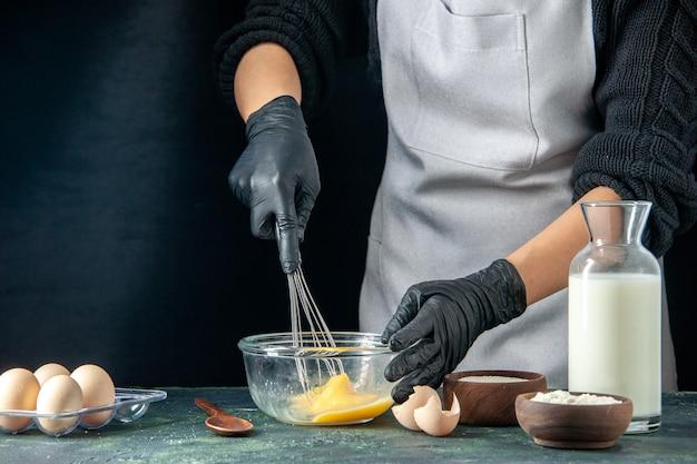 Vooraanzicht vrouwelijke kok die eieren voor deeg mengt op donkere gebak taart taart werknemer keuken baan hotcake