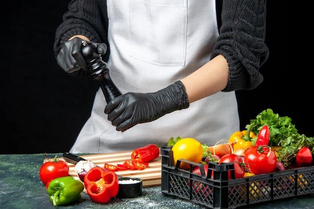 Vooraanzicht vrouwelijke kok die groenten op de donkere maaltijd van de kleurensalade op smaak brengt