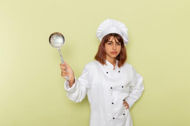 Vooraanzicht vrouwelijke kok die in wit kokkostuum grote zilveren lepel op het groene oppervlak houdt