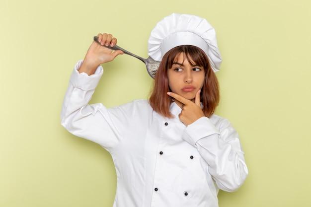 Vooraanzicht vrouwelijke kok die in wit kokkostuum grote zilveren lepel op lichtgroene oppervlakte houdt