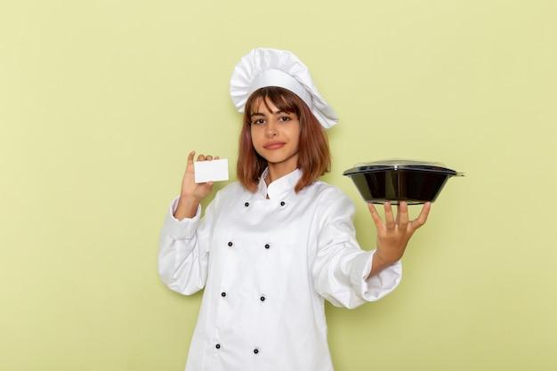 Vooraanzicht vrouwelijke kok die in wit kokkostuum witte kaart en kom op groen bureau houdt