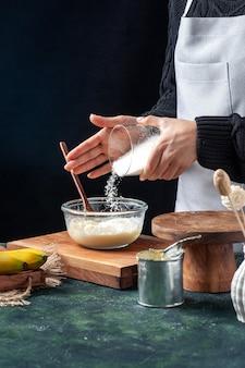 Vooraanzicht vrouwelijke kok die kokosnoot op gecondenseerde melk giet op donkere achtergrond