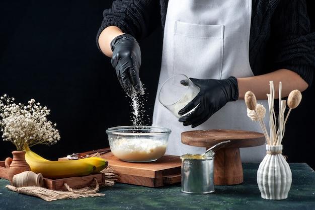 Vooraanzicht vrouwelijke kok die kokospoeder op gecondenseerde melk giet op donkere achtergrond