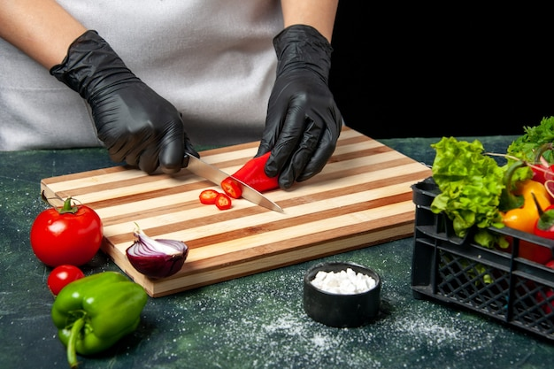 Vooraanzicht vrouwelijke kok die rode peper snijdt op een grijs voedsel koken kleur salade keuken keuken maaltijd kruiden